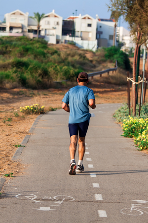 back view of a man running on a road