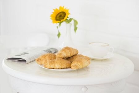 Croissant with a cup of coffee. Newspaper and yellow flower on the table