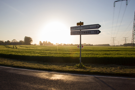 Road in Normandy and distance indicator in km . Sunset Springtime.