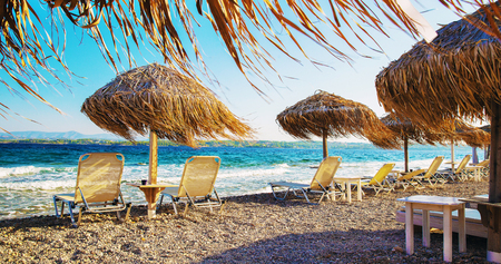 thatched roof umbrellas and lounge chairs by the sea Archivio Fotografico
