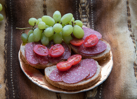 Sandwich with Salami sausage , bread and   small  tomatoes and fresh grapes Reklamní fotografie - 124866876