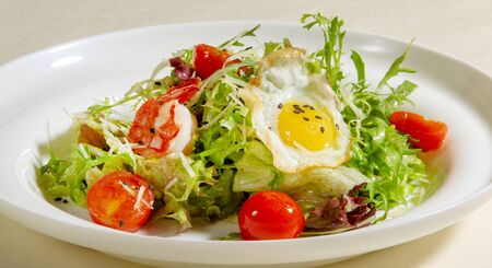 Ensalada de huevo frito, rúcula, tomate y camarones, comida sana.