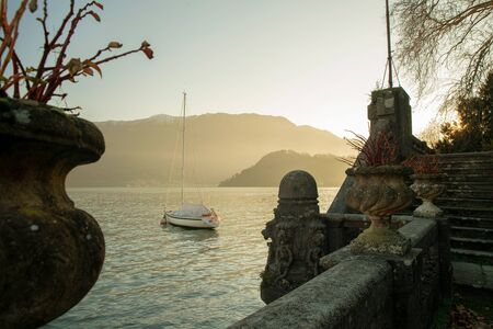 Majestic view on ancient Villa  and sailboat  near on Lake Como.  Soon sunset