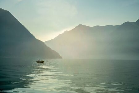 Fisher on lake Como in boat. Mountains  on background. Christmas holiday Stock Photo