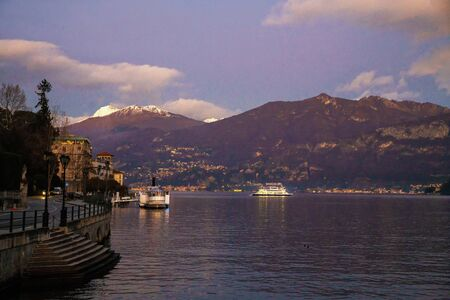 a small ship runs from one settlement to another heading to Como.   Sunset. Quickly becoming dark  on awe lake Como Stock Photo