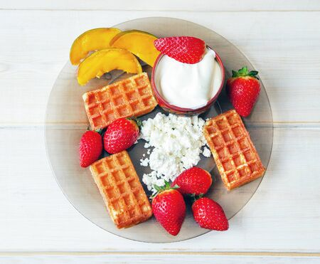 sour cream and cottage cheese and waflles  and strawberries  and pieces of  mango  on white  wooden  boards