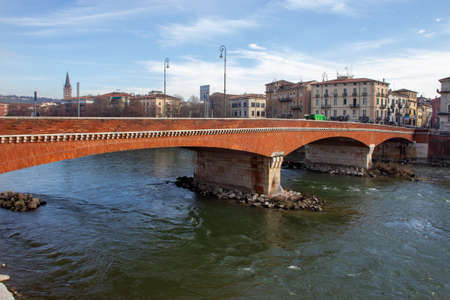 Amazing brick bridge Ponte delle Navi on Adige river. Unrecognizable people walking - fine winter day in Verona!