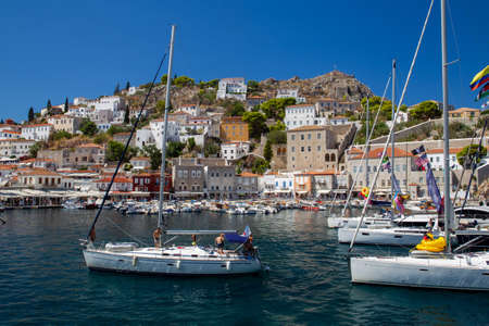09.06.2018 Hydra , Greece . Saling boat moving to harbor of Hydra at sunny summer morning - amazing greek islands!