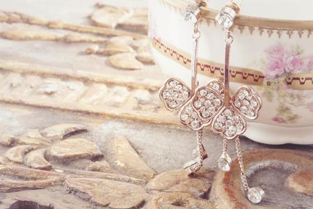 美しい光沢のあるイヤリング ビンテージ背景に掛かっています。