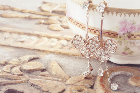 Beautiful shiny earrings hanging on the vintage background