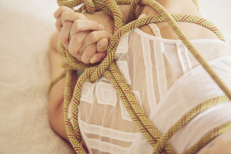 Woman bound with a rope in Japanese technique shibari