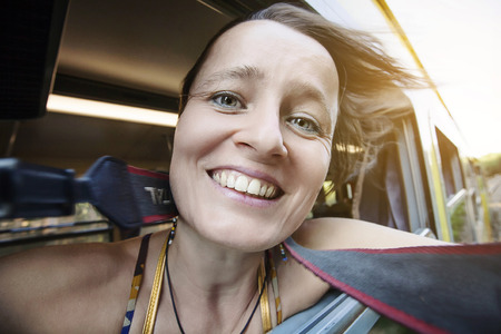 Happy young woman traveling in the train