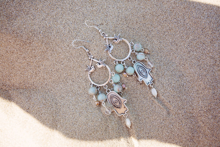 Beautiful earring in the beach sand Stock Photo