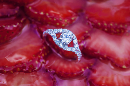 Engagement set of rings on the top of the sweet strawberry cake Stock Photo