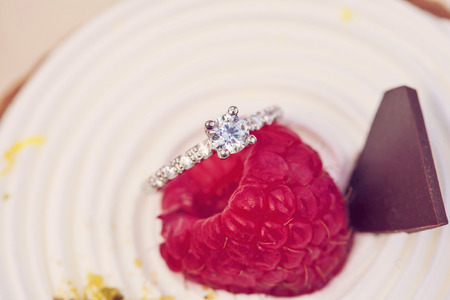 Engagement set of rings on the top of the sweet raspberry cake