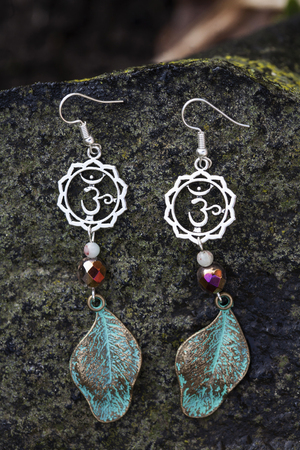 Earrings with burdock leaves and rainbow glass beads Stock Photo - 92153158