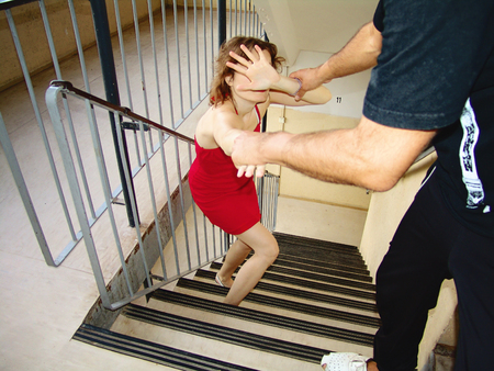 Man attacks a woman on the stairs. Violence against women concept Stock Photo