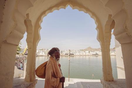 Sadhu Baba with Pushkar holy lake on the background, Pushkar city, Rajasthan, India, February 15, 2018 Publikacyjne