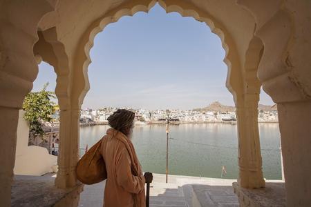Sadhu Baba with Pushkar holy lake on the background, Pushkar city, Rajasthan, India, February 15, 2018 Editorial