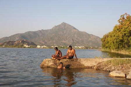 Tiruvannamalai / Tamil Nadu / India, February 1, 2018: Young Indians taking bath in the lake next to Arunachala mountain