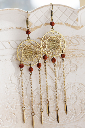 Spiritual Brass Earrings on vintage background Stock Photo