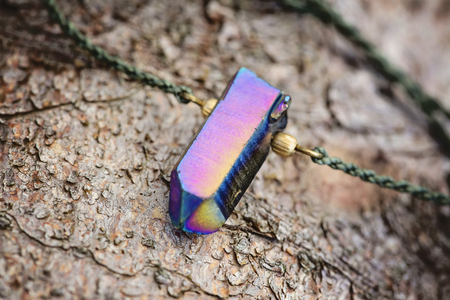 Crystal quartz pendant necklace detail on wooden background