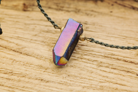 Crystal quartz pendant necklace detail on wooden background