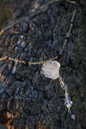 Antique chain natural crystal quartz pendant necklace on wooden background Reklamní fotografie