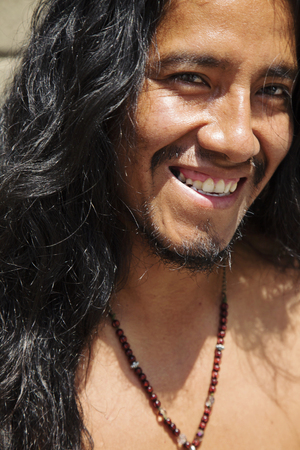 City portrait of young latino man with long hair and jewelry 版權商用圖片