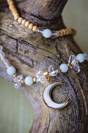 Moon pendant mineral stone beads necklace on wooden background