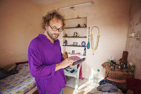 Arunachala, Tiruvannamalai in Tamil Nadu, India, January 30, 2018: European seeker in his rental apartment close to Arunachala mountain looking at his cellphone