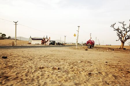 Pushkar Desert, Rajasthan, India, February 2018: Pushkar desert with camels and vehicles