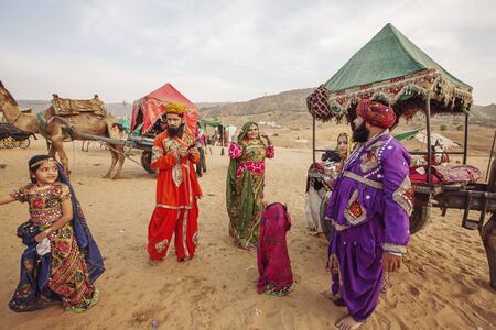 Pushkar Desert, Rajasthan, India, February 2018: Traditinally dressed family with camels and vehicle at Pushkar desert Editorial