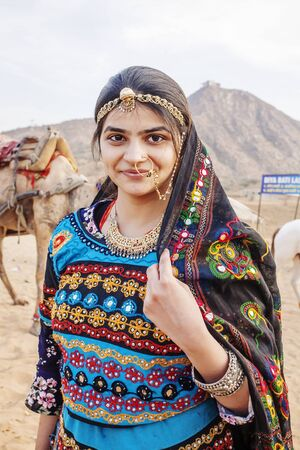 Pushkar Desert, Rajasthan, India, February 2018: Traditinally dressed young Indian woman with camels and vehicle at Pushkar desert