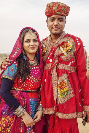 Pushkar Desert, Rajasthan, India, February 2018: Traditinally dressed young Indian couple with camels and vehicle at Pushkar desert