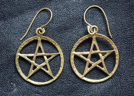Metal pentagram earrings on black background Stock Photo - 119804347