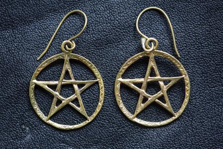 Metal pentagram earrings on black background Stock Photo