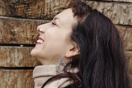 Outdoor close up portrait of beautiful woman wearing silver earrings Imagens