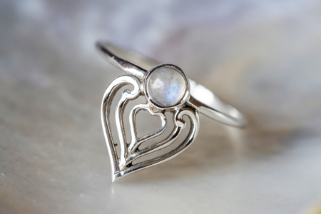 Elegant female silver ring on natural shell nacrous background