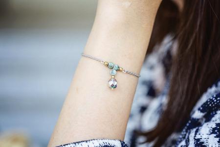 Polso femminile che indossa un piccolo braccialetto di gioielli con perline di pietra minerale Archivio Fotografico