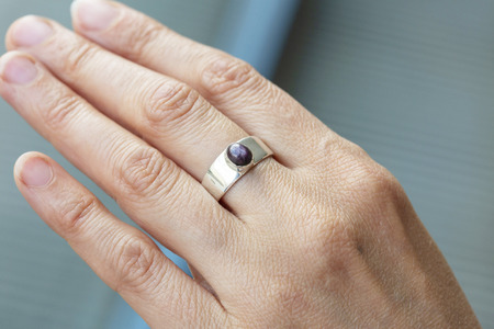 Female hand wearing silver ring with ruby star gemstone Banco de Imagens