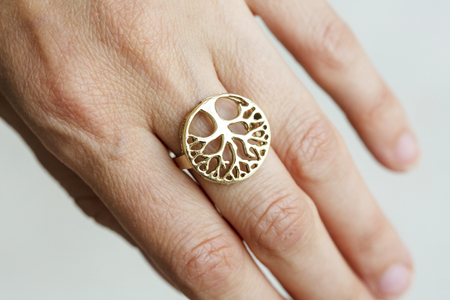 Female hand wearing brass ring in the shape of tree Standard-Bild