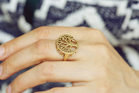 Female hand wearing brass ring in the shape of tree 版權商用圖片