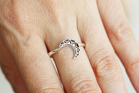 Female hand wearing silver ring in the shape of moon