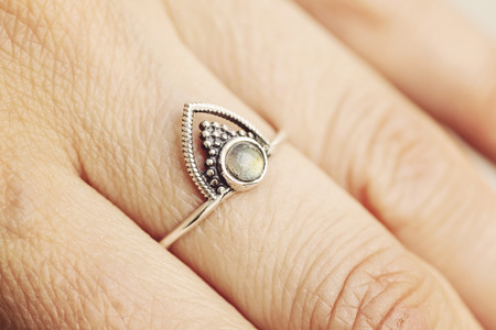 Kobieca ręka nosząca srebrny pierścionek z kamieniem labradorytu