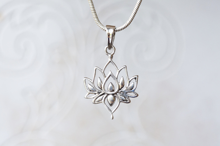 Silver lotus pendant on natural white background Imagens