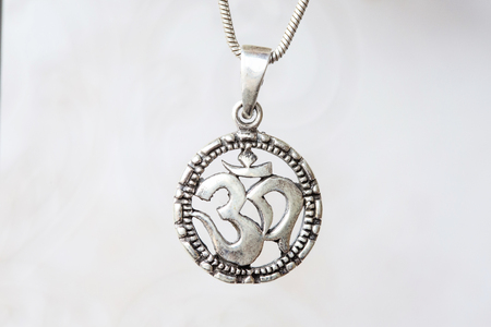 Silver om pendant on natural white background