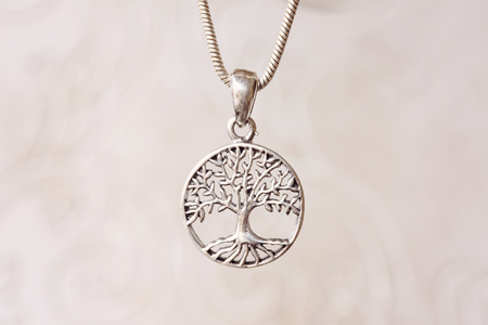 Silver tree in madala pendant on natural white background Imagens