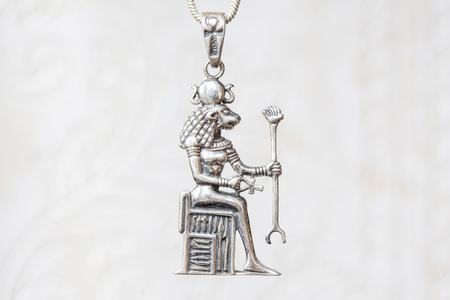 Silver Egyptian god pendant on natural white background