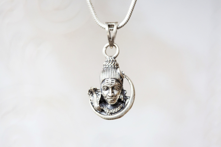 Silver Shiva head pendant on natural white background